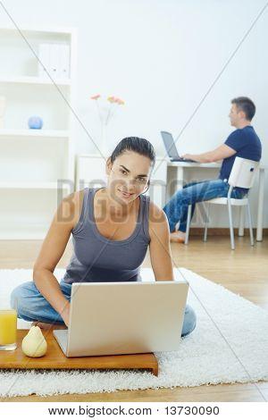 Junge Frau sitzen auf Boden zu Hause mit Laptop-Computer, lächelnd.?