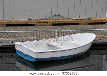 Old blue and white rowboat tied to dock