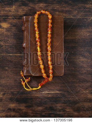 book in a vintage leather bound, and amber beads