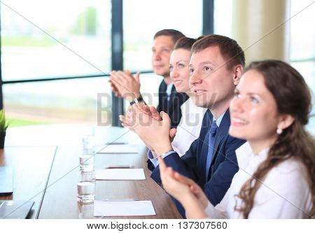 Image of business colleagues applauding in the end of the conference sitting in a line