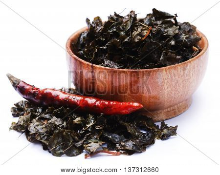 Fried moringa leaves in a bowl over white background