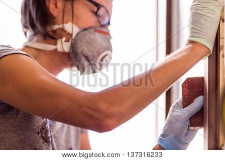 Woman In Gloves Sanding Frame Around Door
