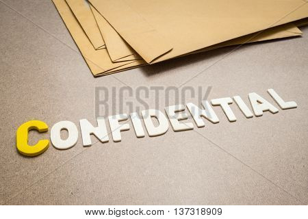 Confidential wording on brown background with pile of brown envelope in the background