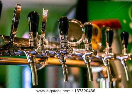 Beer taps in a pub. Close up of beer Tap. Selective focus.