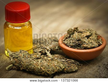 Medicinal cannabis with extracted oil in a bottle