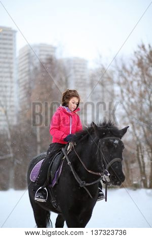 Portrait of young girl on a black horse at the winter equestrian site in front of trees and buildings