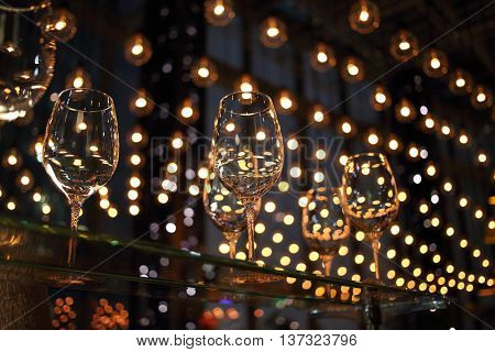 Wine glasses on a glass table illuminated lots of luminous lamps
