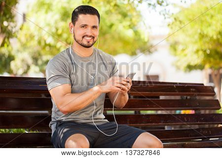Latin Young Man Listening To Music In A Park