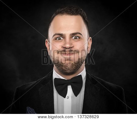 Man in suit makes funny face over dark background