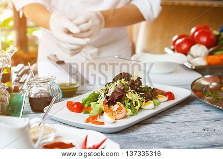 Salad on white plate. Man standing near salad plate. Salad recipe with shrimp. European cuisine at the restaurant.