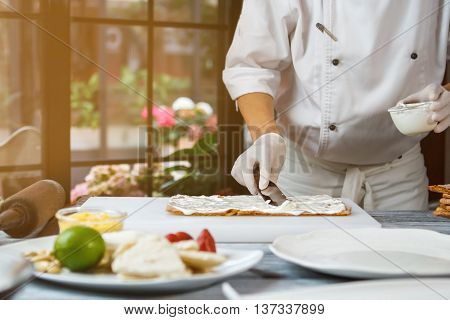 Spatula putting cream on shortcake. Hand holds bowl with cream. Preparation of high-calorie dessert. Chef knows correct proportions.