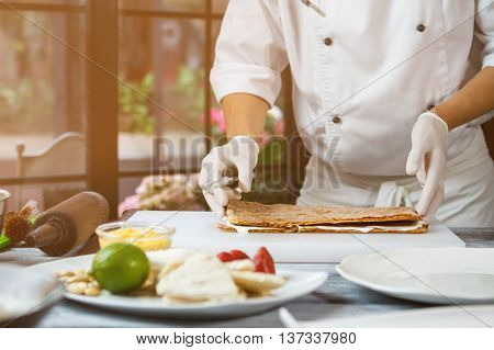 Man's hands touch shortcake dough. Thin layers of dough. Chef prepares a cake. Special recipe of tasty dessert.
