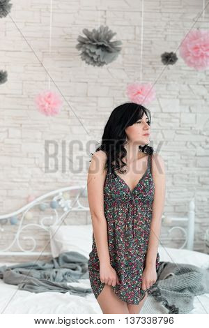 Wistfully looking brunette woman in sarafan. Young beautiful woman in bedroom reflectively standing near bed. Serious woman rumpling her dress