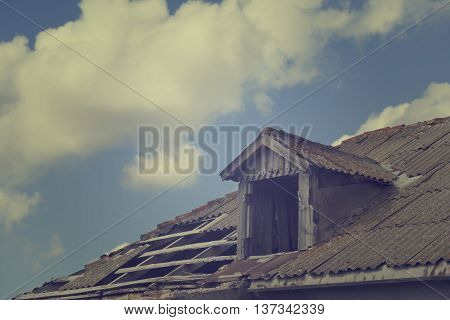 Old tile roof with holes and sky with clouds. Toned landscape.