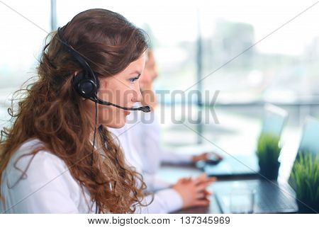Portrait of smiling female customer service agent wearing headset with colleagues working in background at office