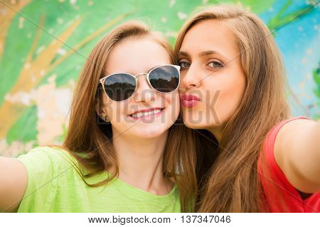 Closeup portrait of two teenage girls friends in hipster outfit having fun kissing and taking a selfie. Outdoors lifestyle.