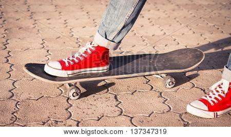 Legs in red sneakers on a skateboard.