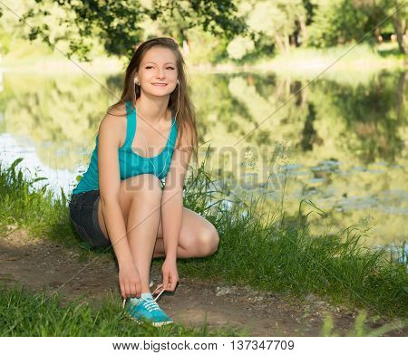 Closeup of young woman tying shoe laces. Female sport fitness runner getting ready for jogging outdoors on forest path near the river in spring or summer.