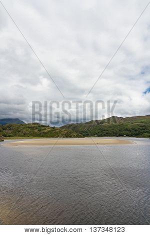 View of the River Dwyryd near Penrhyndeudraeth. Sand bank trees and rocky hills. Gwynedd Snowdonia Wales United Kingdom.