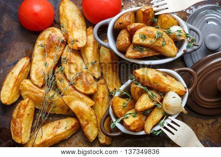 Baked potato wedges with spices garlic and thyme on a metal baking sheet and portion pots . Top view