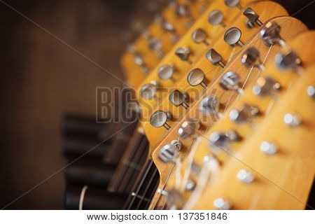 Electric guitar head stocks on a guitar rack. Shallow depth of field.