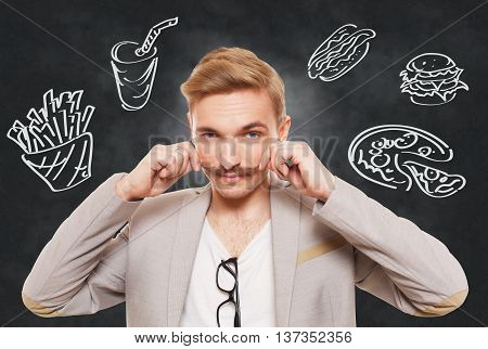 Handsome man and fast food temptation. Unhealthy food craving. Pizza, hamburger, hot dog, french fries and cola drink desire. Young guy with moustache and fast food drawing at blackboard background