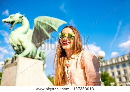 Young smiling traveler sitting on the with Dragon bridge in Ljubljana city. Dragon statue is one of the most famous symbols of the capital of Slovenia