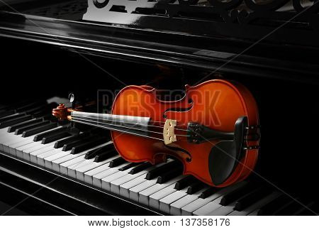 Violin lying on piano keys, close up