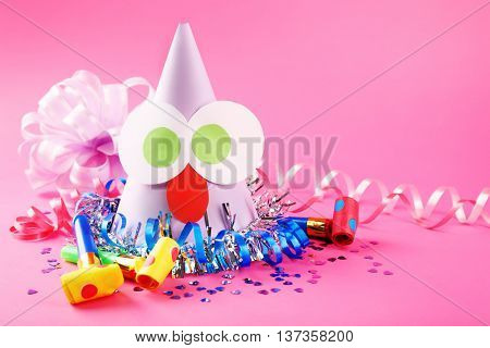 Funny party hat with blowers on pink background