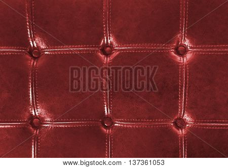 Close up of rich red tufted leather upholstery with buttons.