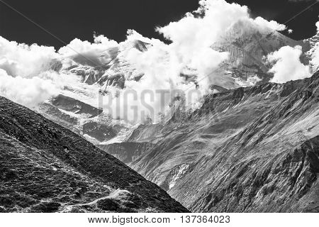 Snow covered mountain top engulfed in clouds. Annapurna region in Himalaya.