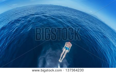 Man swimming on the breath hold in the open sea.
