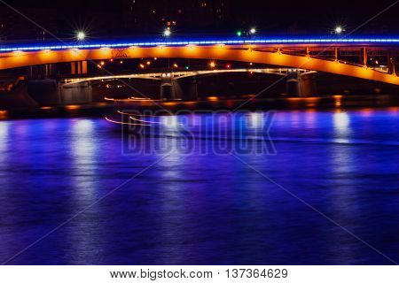 Part of a bridge across the Moscow River with light and reflection in the water, night scene. Art Effect light blur.