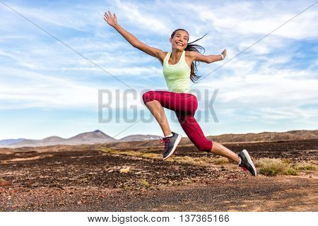 Success freedom carefree runner woman running fun. Happiness, joy, energetic athlete girl happy of weight loss goal achievement jumping funny on summer outdoor trail nature. Fitness motivation.
