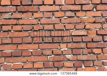 Old wall from red brick. Red clay brick. Brick wall. The old crumbling brick wall. Bricks and stones in the old wall. The old brick wall collapses and urgent repair is necessary.