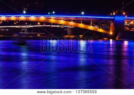 Part of a bridge across Moscow river with bright blue light reflection on water surface at night time