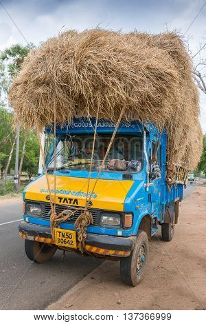 Madurai India - October 18 2013: A blue TATA Truck is overloaded with rice straw and parked off the road. Crew in cabin front view.