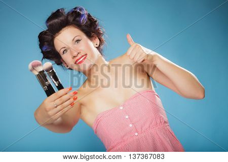Cosmetic beauty procedures and makeover concept. Woman in hair rollers holding makeup brushes set making thumb up gesture on blue