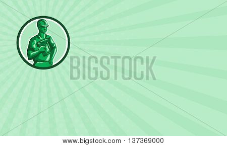 Business card showing illustration of a green plastic toy construction worker standing wearing hard hat holding nailgun and other hand on hips set inside circle on isolated background done in retro style.