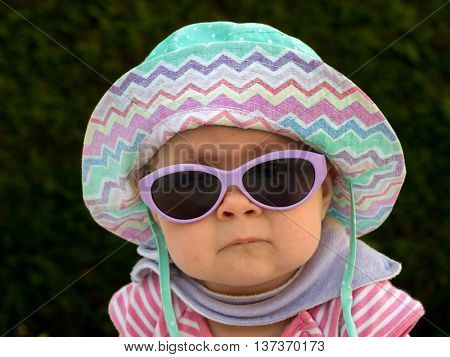 baby with sun hat and sunglasses in the garden