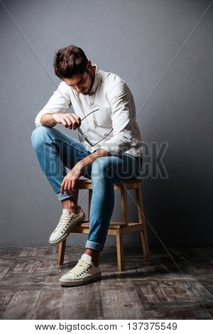 Sad upset young man sitting and looking down over grey background