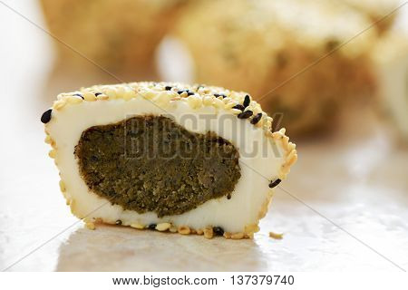 closeup of a Japanese sesame mochi pastry cut in half, and some other mochi pastries in the background