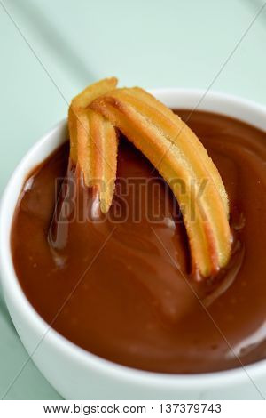 closeup of a churro soaked in hot chocolate, a typical Spanish sweet snack known as churros con chocolate, on a blue rustic wooden table