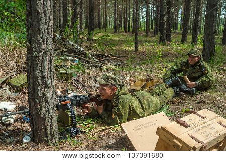 Tyumen, Russia - June 11, 2016: Race of Heroes project on the ground of the highest military and engineering school. Machine gunners ambush in forest