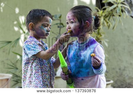 Brother and sister with their face smeared with colors celebrating Holi festival in India.