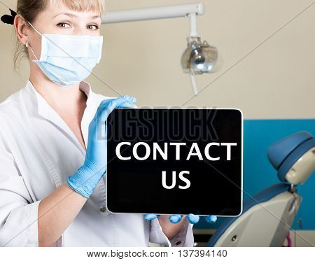 technology, internet and networking in medicine concept - femail dentist holding a tablet pc with contact us sign. at the dental equipment background.