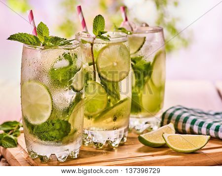 Alcohol drink. On wooden boards three glasses with alcohol drink and ice cubes. A drink number forty seven cocktail mohito with knife and mint leaf. Country life. Light background.