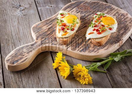 scrambled eggs with bread on cutting board closeup