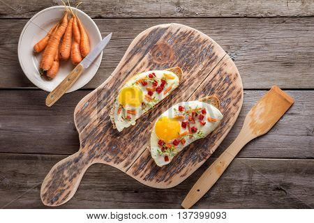 scrambled eggs with bread on cutting board top view