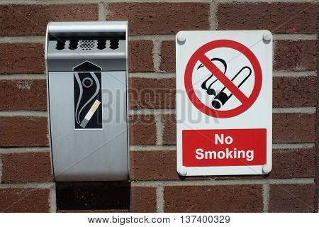 No smoking sign and waste cigarette receiving bin on wall.